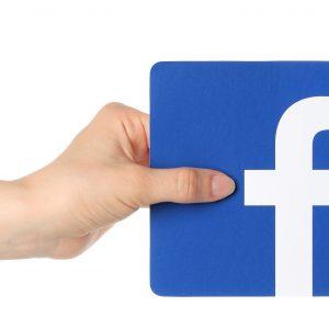 Hand grabbing Facebook